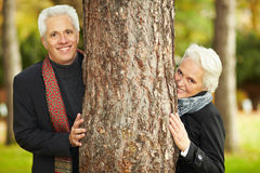 Two senior citizens behind a tree Stock Image