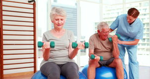 Two senior citizens exercising with physiotherapist stock video