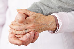 Two senior citizens holding hands Royalty Free Stock Photos