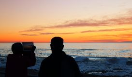 Two senior citizens using technology to capture gorgeous spring sunset over Lake Huron royalty free stock photography