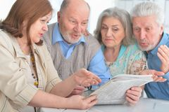 Portrait of two senior couples sitting at table and reading newspaper royalty free stock photography