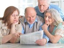 Senior couples reading newspaper. Two senior couples sitting at table and reading newspaper Royalty Free Stock Images