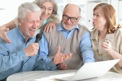 Portrait of two senior couples reading newspaper royalty free stock photography