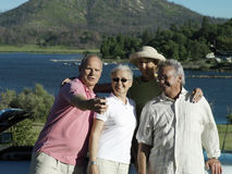 Two senior couples standing beside car near lake, man taking photograph with digital camera, smiling Royalty Free Stock Photos
