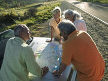 Two senior couples standing beside convertible car, looking at road map, elevated view Stock Photography
