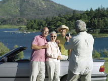 Two senior couples standing beside convertible car near lake, smiling, man filming with camcorder Stock Photos