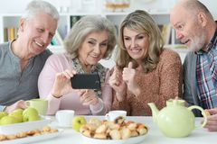 Two  Senior couples using smartphone during morning tea. At kitchen table royalty free stock image