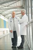 Two senior doctors talking in hospital hallway. Two senior doctors talking in the hospital hallway stock photography