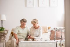 Two senior friends sitting together at couch stock photography