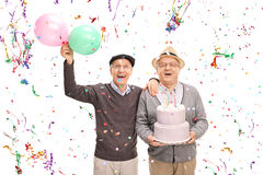 Two senior gentlemen celebrating birthday. With a cake and balloons isolated on white background royalty free stock images
