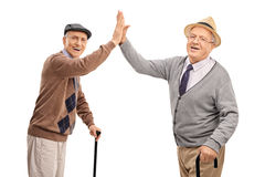 Two senior gentlemen high-five each other Stock Image