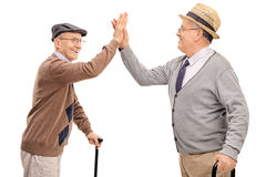 Two senior gentlemen high-five each other. Two joyful senior gentlemen high-five each other isolated on white background royalty free stock image