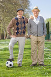 Two senior gentlemen posing with a football. Full length portrait of two senior gentlemen posing in a park with a football on a sunny day royalty free stock photos