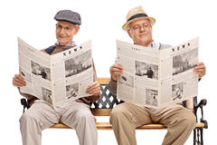 Two senior gentlemen reading newspapers. Two senior gentlemen sitting on bench and reading newspapers isolated on white background Royalty Free Stock Photography