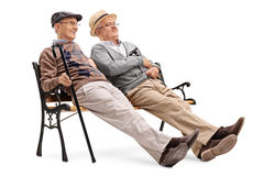 Two senior gentlemen sitting on a bench. Two relaxed senior gentlemen sitting on a bench isolated on white background Stock Photos
