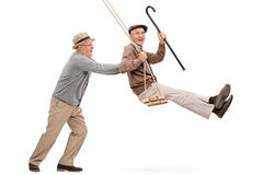 Two senior gentlemen swinging on a swing Stock Photography