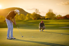 Two senior golf player at sunset. Royalty Free Stock Images