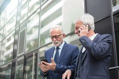 Two happy senior businessmen using smart phones, talking and messaging royalty free stock photography