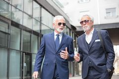 Two senior businessmen walking down the street, discussing stock photography