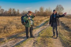 Two senior hikers with backpacks discussing correct path while walking on a country road. At autumnal evening stock image