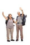 Two senior hikers waving at the camera Royalty Free Stock Image