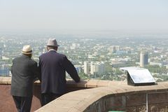 Two senior kazakh men talk and enjoy the view to Almaty city in Almaty, Kazakhstan. Stock Image