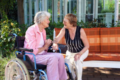 Two senior ladies chatting on a garden bench. Two senior ladies chatting on a garden bench with one sitting in a wheelchair at the end as they enjoy a day royalty free stock image