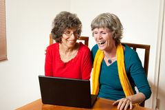 Two senior ladies laughing surfing Royalty Free Stock Image
