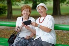 Two senior ladies reading news on tablet PC Stock Photo