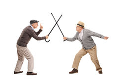 Two senior man in a sword fight with canes. Studio shot of two senior gentlemen having a sword fight with their canes isolated on white background stock image
