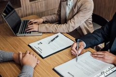 Two senior manager reading a resume during a job interview, Employer interviewing to ask young male job seeker for recruitment ta. Lking in office stock photo