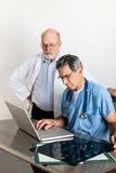 Two Senior Medical Doctors Discussing Patient's MRI Film Scans stock photo