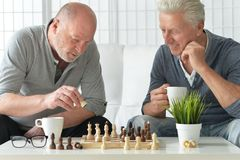 Senior men playing chess. Two senior men having fun and playing chess at home royalty free stock photography