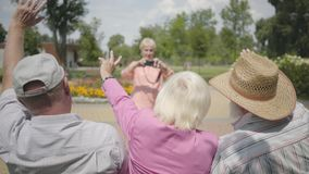 Two senior men and one woman waving hands while the fourth woman taking a photo of them in the park. Mature people. Two senior men and one woman waving hands stock video