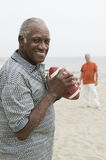 Two senior men playing american football on beach Royalty Free Stock Photo