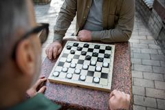 Two senior men playing checkers outdoor Royalty Free Stock Photo