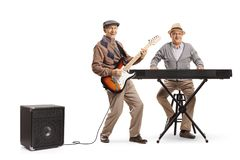 Two senior men playing keyboard and an electric guitar. Full length portrait of two senior men playing keyboard and an electric guitar isolated on white royalty free stock photo