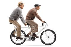 Two senior men riding a tandem bicycle. Full length profile shot of two senior men riding a tandem bicycle isolated on white background stock image