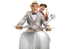 Two senior men riding on a vintage scooter and showing thumbs up stock photography