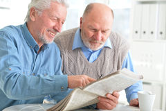 Two senior men sitting at table and reading. Newspaper royalty free stock image
