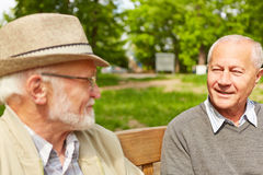 Two senior men talking to each other. In a park of a retirement home stock photo