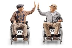 Two senior men in wheelchairs giving high-five. Isolated on white background stock image