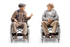 Two senior men in wheelchairs having a conversation. Isolated on white background stock image