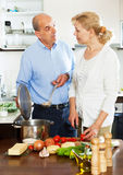 Two  senior people cooking in the kitchen Royalty Free Stock Photo