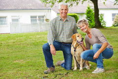 Two senior people with dog in front of house. Two smiling senior people sitting with dog in front of their house in the garden Stock Photos