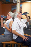 Two senior people drinking water. Two senior people in a gym drinking water Royalty Free Stock Image