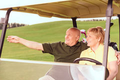 Two senior people driving in cart. Look there. Senior smiling men and women driving in cart on course, men pointing aside with help of his hand Stock Image