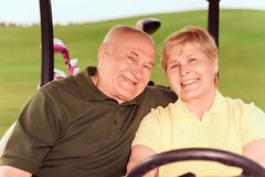 Two senior people driving in cart. To next hole. Portrait of senior men and women driving in cart on course Stock Image