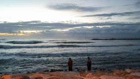 Two senior people fishing and sunset. Two senior people with fish-rods standing and try to catch fish, sunset, winter weather, Mediterranean Sea, Haifa Royalty Free Stock Photography