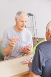Two senior people playing cards Stock Photos